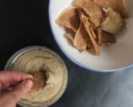 dipping a chip in hummus