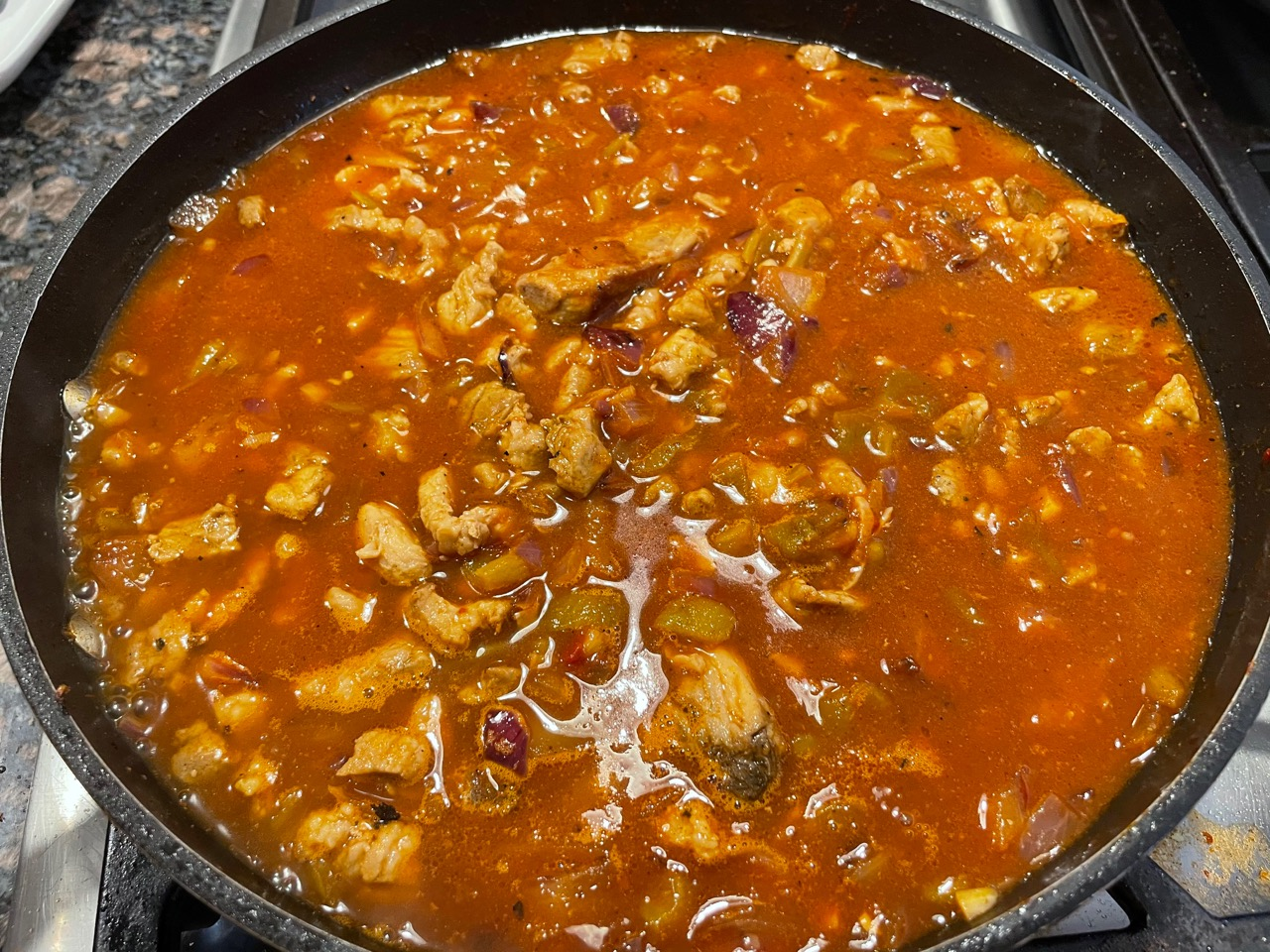 adding tomato paste to cooked meat