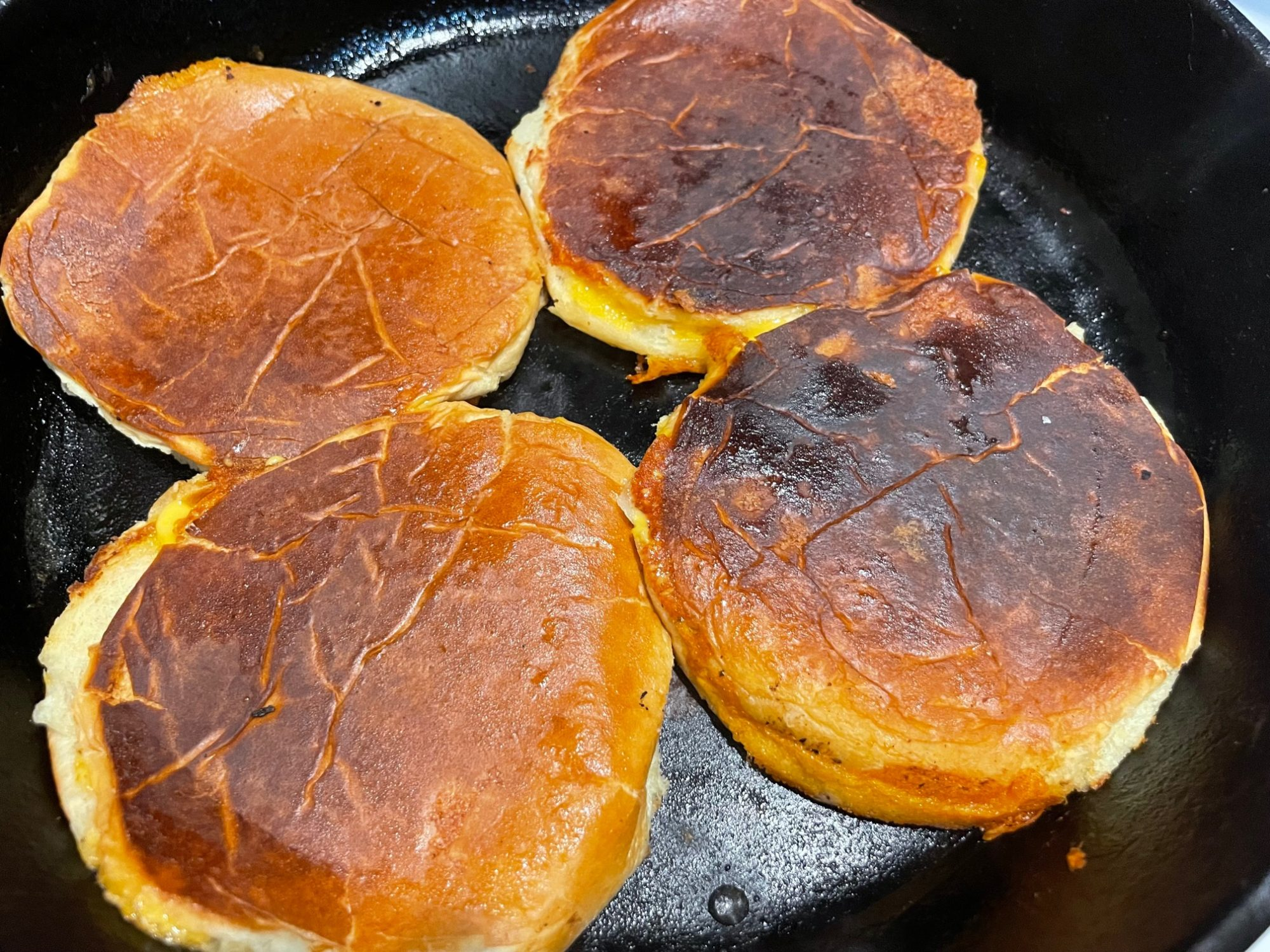 grilled cheese buns in the pan cooked and smooshed!